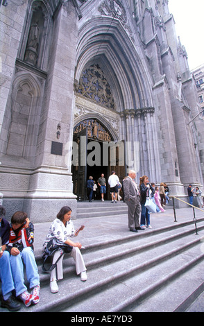 People standing outside the main entrance to St Patricks Cathedral seat of the Archbishop of New York and largest - Stock Photo