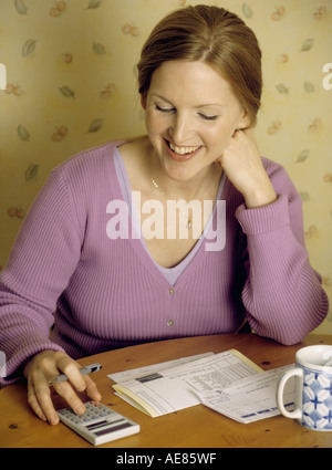 Young woman checking bills using a calculator looking happy - Stock Photo