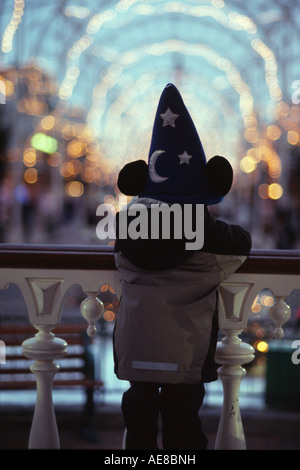 boy standing looking down main street usa with disney hat on in the winter - Stock Photo
