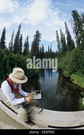 Flyfisherman choosing fly on bridge overlooking stream Bulkley Valley British Columbia - Stock Photo