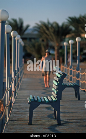 Woman walkign towards an empty seat on a jetty Red Sea coast at Nuweiba Sinai Egypt Vacation photograph Middle East - Stock Photo