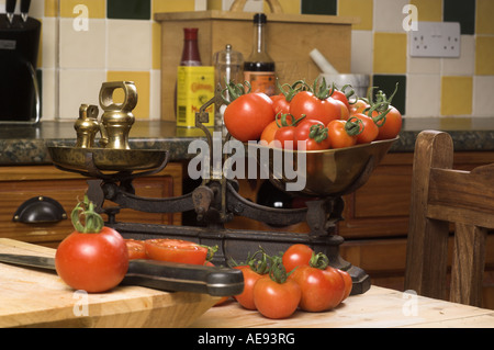 Home grown Tomatoes in a traditional country kitchen with rustic scales - Stock Photo