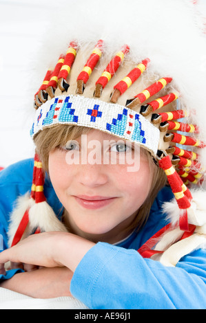 Portrait of a young boy looking at the camera, with indian headdress - Stock Photo