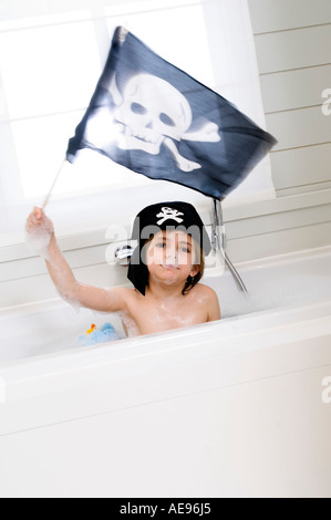 Little boy in bath holding pirate flag - Stock Photo
