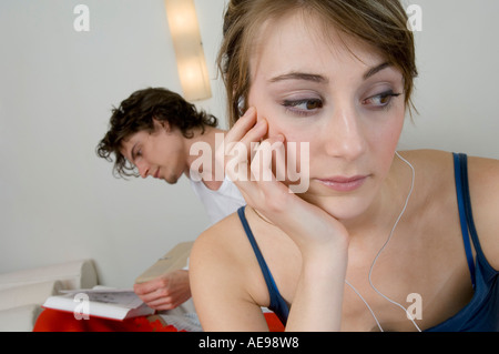 Couple sitting on a bed, thinking woman wearing s, man reading in background - Stock Photo