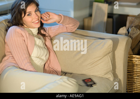 Young woman sitting on a sofa,  MP3 player, smiling for the camera - Stock Photo