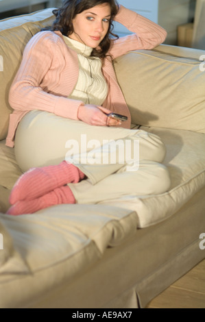 Young woman sitting on a sofa,  MP3 player - Stock Photo