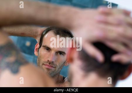 Tattooed man, barechested, looking in bathroom mirror - Stock Photo