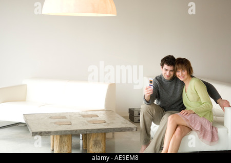Smiling couple sitting on a sofa, taking picture with camera phone - Stock Photo