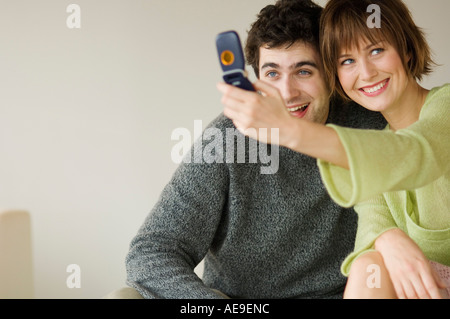 Smiling couple taking picture with camera phone - Stock Photo