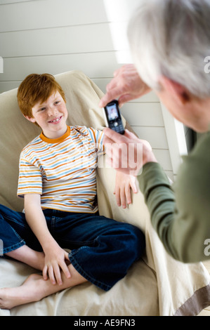 Senior man taking picture of smiling boy with camera phone - Stock Photo