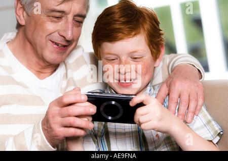 Senior man and boy playing Playstation Portable - Stock Photo