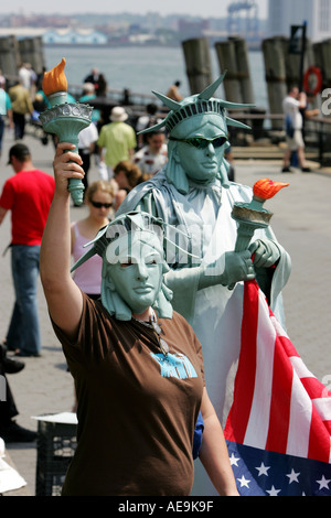 Tourists take pictures with a person dressed like the statue of Liberty in New York City - Stock Photo