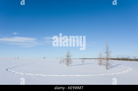 Footpath on fresh new snow and silhouetted two persons walking at the top of the hill , Finland - Stock Photo