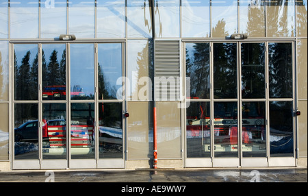 Fire department trucks behind closed garage glass doors , Finland - Stock Photo