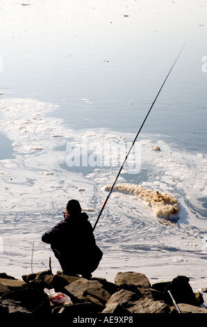 A man fishing in a dirty river water filled with foam and peat residue from a power plant , Finland - Stock Photo