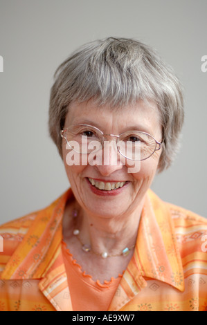 Studio portrait of elderly woman with glasses smiling at camera - Stock Photo