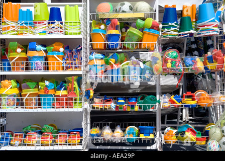 A row of brightly coloured seaside toys on sale outside a tourist gift shop - Stock Photo
