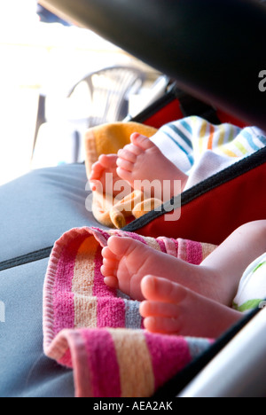 a close up of twin babies feet in pram - Stock Photo