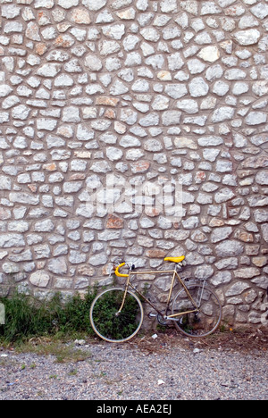a retro mens racing bicycle stands propped up against an old stone wall in the south of france - Stock Photo