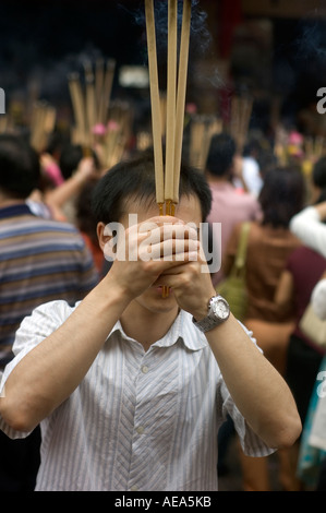 A Chinese man holding burning incense sticks in front of a praying crowd during the Chinese New Year celebration. - Stock Photo