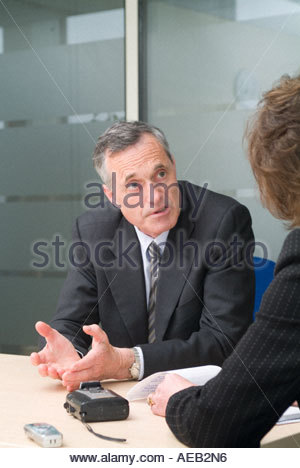 Boardroom Meeting management in discussion white middle aged man and female with hands on table - Stock Photo