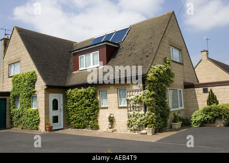 Modern solar thermal hot water panels with evacuated tubes on roof of detached house Cotswolds UK - Stock Photo