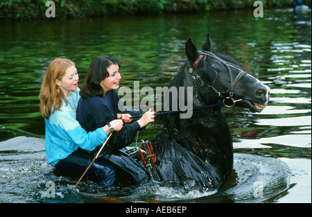 Two romany girls ride their horse in the River Eden at Appleby, Cumbria during the annual Appleby Horse Fair, UK - Stock Photo
