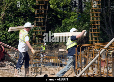 Construction workers on building site carrying materials, Milton Keynes, UK. - Stock Photo
