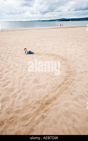 9 month old baby girl crawls on Exmouth beach East Devon UK - Stock Photo