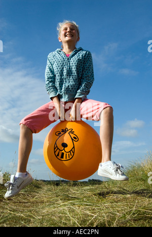 Young girl bouncing on a Space Hopper England UK - Stock Photo