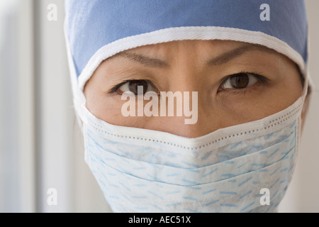 Close up of Asian female doctor wearing surgical mask - Stock Photo