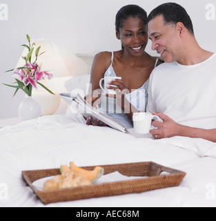Middle-aged African couple having breakfast in bed - Stock Photo