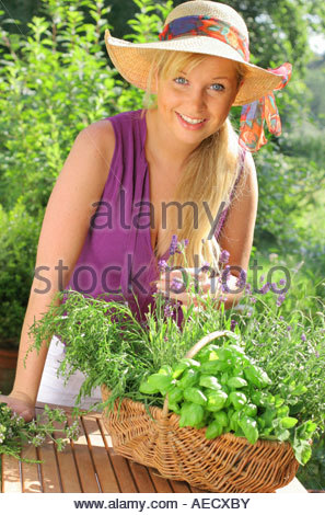 young blonde woman with basket full of herbs - Stock Photo