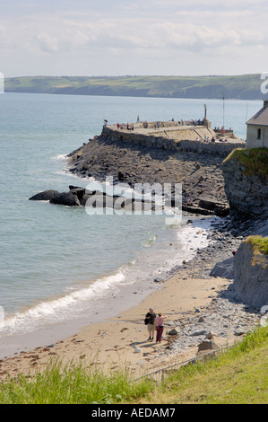 Visitors on Beach Harbour Wall New Quay Ceredigion West Wales - Stock Photo