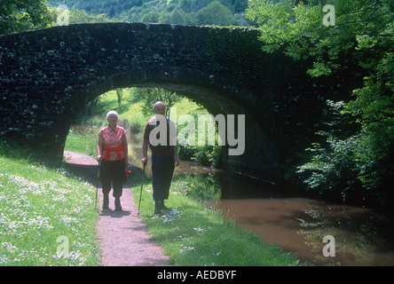 Couple Walking along Monmouthshire and Brecon Canal near Talybont on Usk Brecon Beacons Mid Wales - Stock Photo