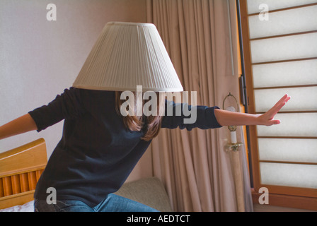 Young woman pretending to surf with a lampshade on her head acting stupid - Stock Photo