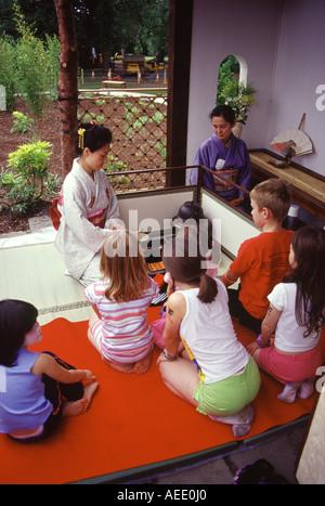 Children watching a Japanese tea ceremony in a formal Japanese garden, Lauriston Castle, Edinburgh, Scotland UK - Stock Photo
