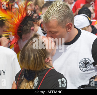 Two German football fans kissing at a football world cup public viewing event in Dortmund - Stock Photo