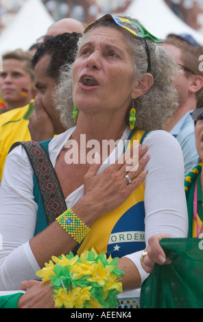 A female Brazilian football fan singing her national anthem at a public viewing event before the world cup match - Stock Photo