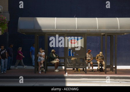 Street scenes with pedestrians and buildings in downtown Columbus Ohio People waiting at a bus stop - Stock Photo