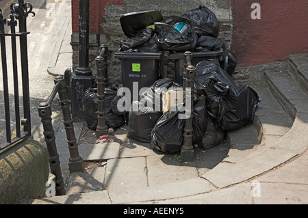 Overflowing black rubbish bags and wheely bin waiting for collection and blocking path Bristol England - Stock Photo