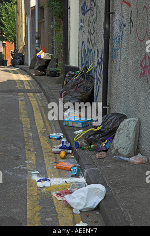 Overflowing broken black rubbish bags waiting for collection and blocking path Bristol England - Stock Photo