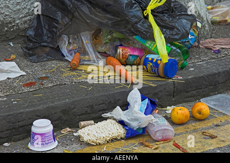 Overflowing broken black rubbish bag with spilled food waiting in vain for collection and blocking path Bristol - Stock Photo