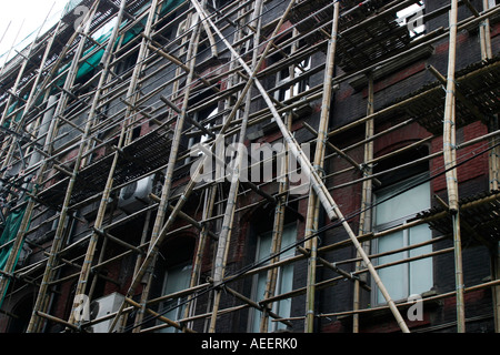 Bamboo scaffolding Shanghai China - construction workers still use bamboo scaffolding on some smaller building sites - Stock Photo