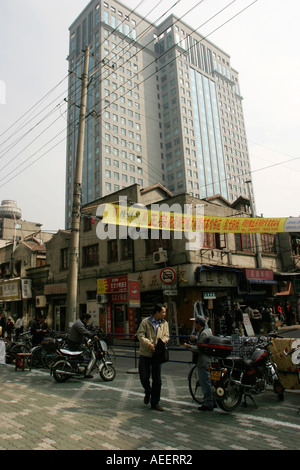 Old shop and skyscraper in Shanghai China.  Old shops continue to trade in central Shanghai as new buildings replace - Stock Photo