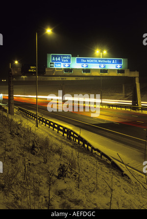 headlight trails of traffic travelling on the a1 m1 motorway in wintertime at night near leeds uk - Stock Photo