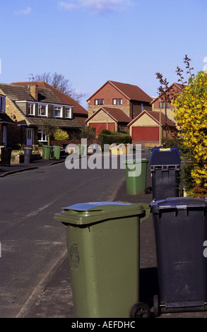 household waste bins and green recycling wheelie bins left out on pavement awaiting collection yorkshire uk - Stock Photo