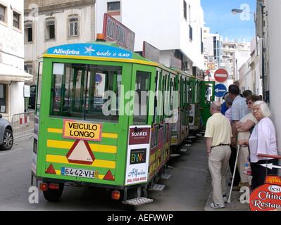 Passengers wait to board a train like bus in albufera portugal - Stock Photo