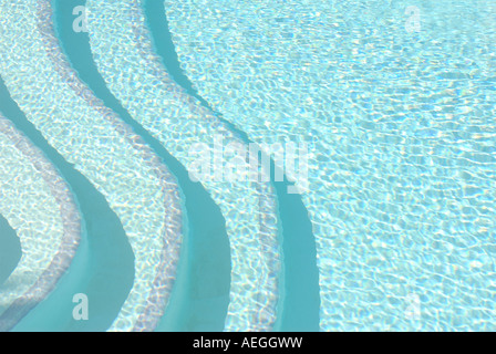 Contemporary patterned bold image of swimming pool steps seen above the water - Stock Photo